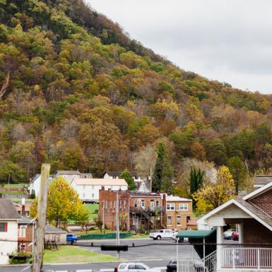 A rural town with a hillside in the background