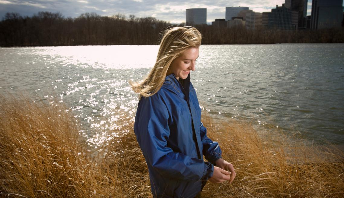 Woman standing next to river with buildings in background.