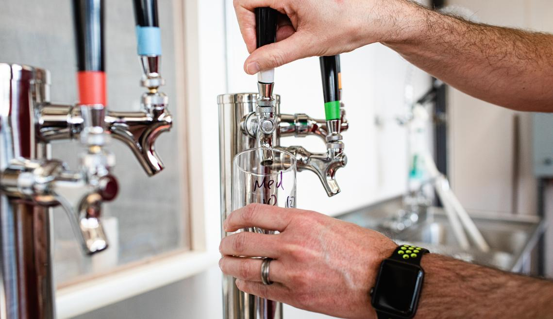 Person pouring beer from a tap.