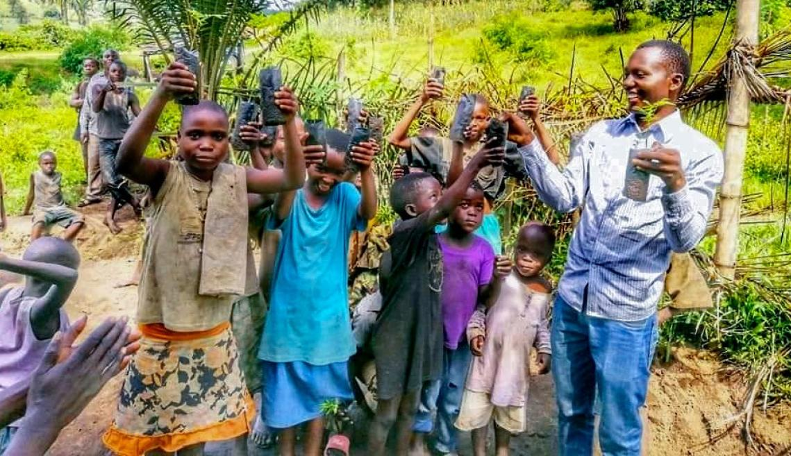 A man standing with children outside holding up small tree plantings