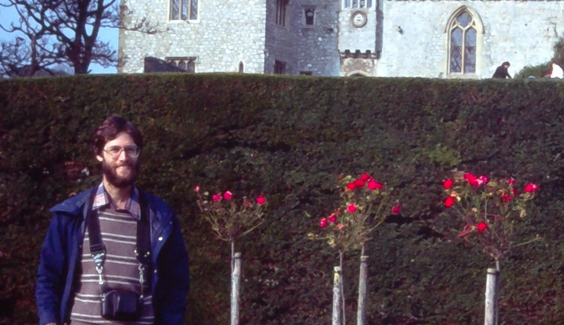 A man stands in front of a castle in the mid-1970s