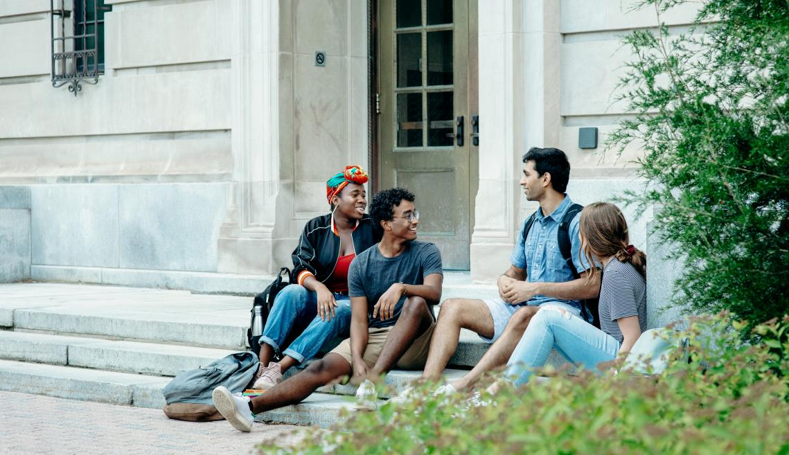 Students sit outside of the Charles H. Dyson School of applied economics and management.