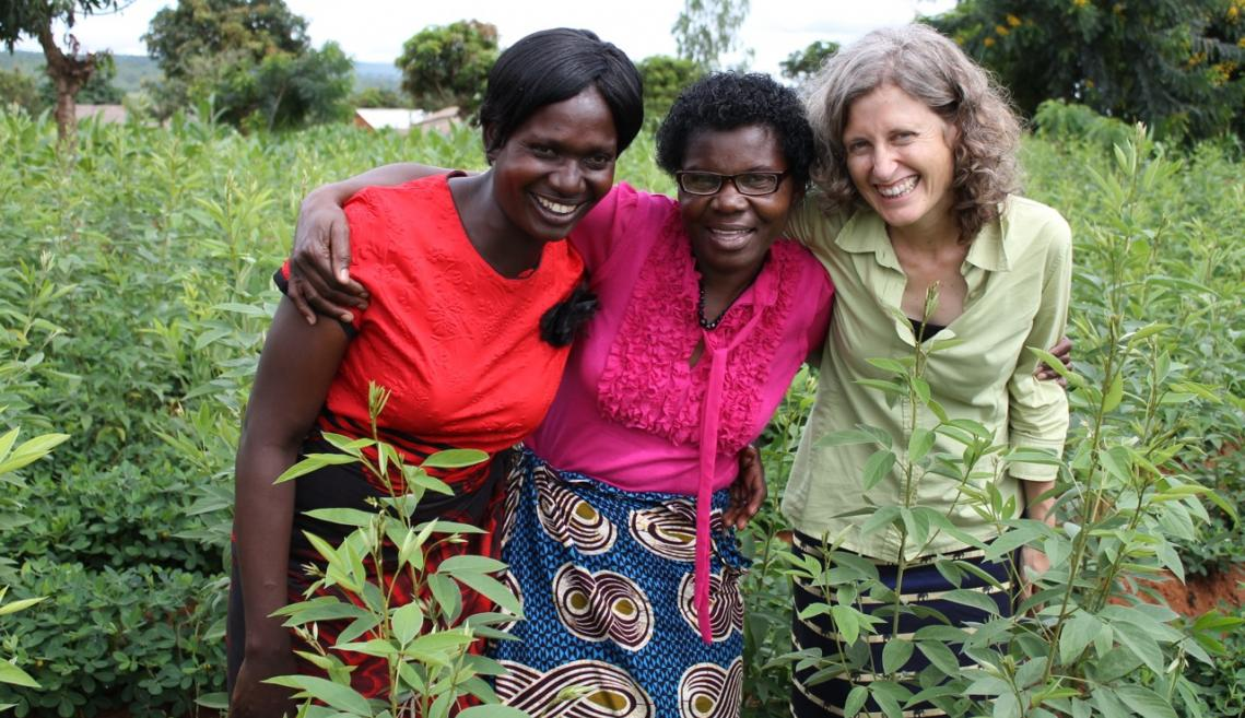 Three women stand in field in Malawi