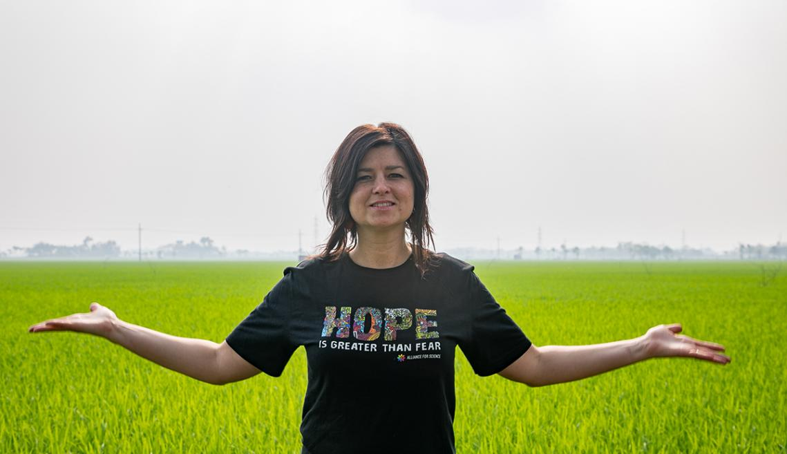 """Woman stands in rice field wearing """"hope"""" shirt"""