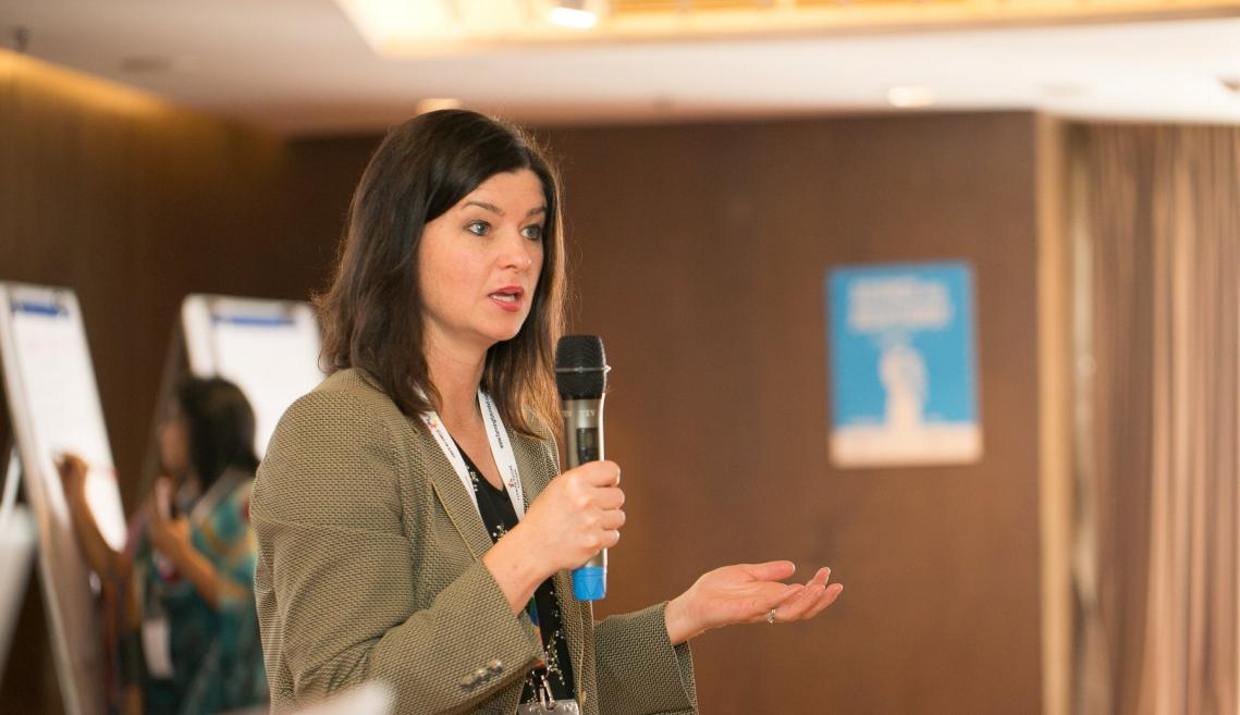 Woman holds microphone and gives speech at a conference