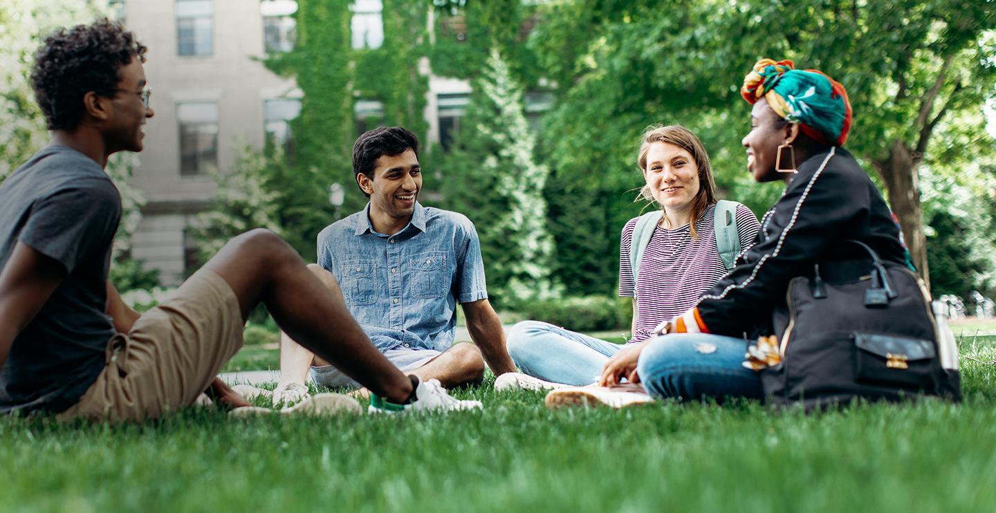Four students sit in the lawn and talk
