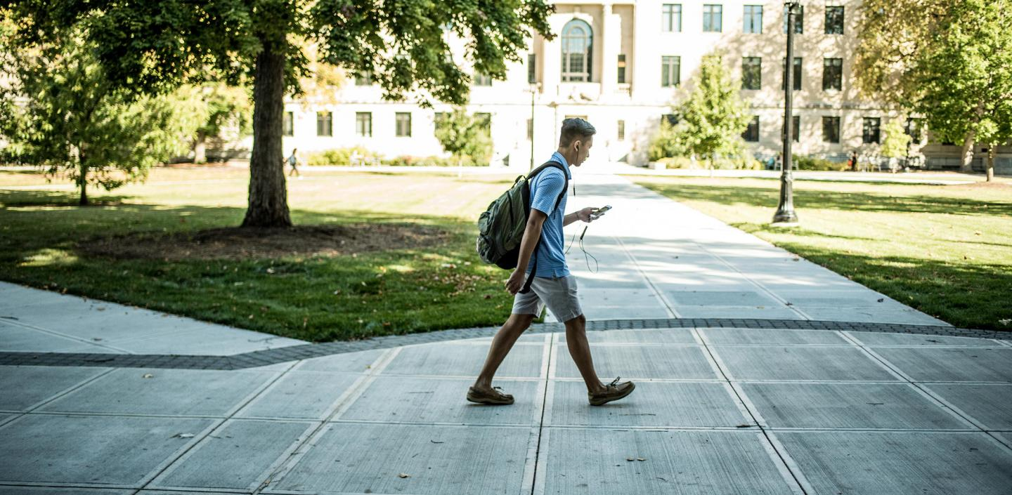 Student on phone walking through campus