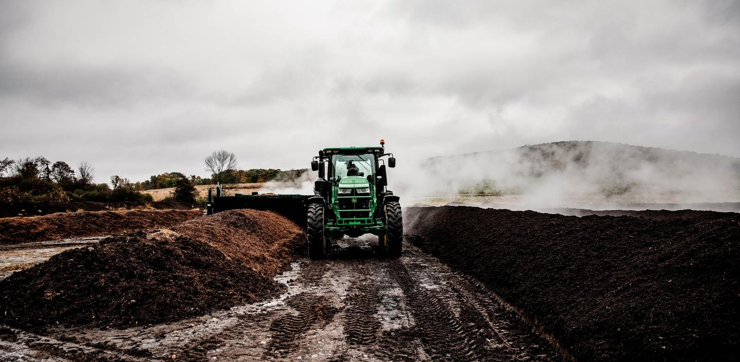 Tractor turning compost at outdoor facility.