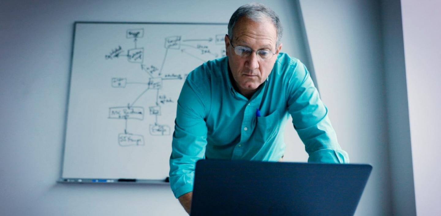 An older man with glasses and wearing a blue shirt standing over and working at a laptop with a whiteboard behind him