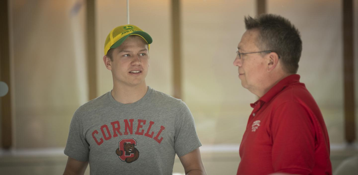 Two men in Cornell shirts talking