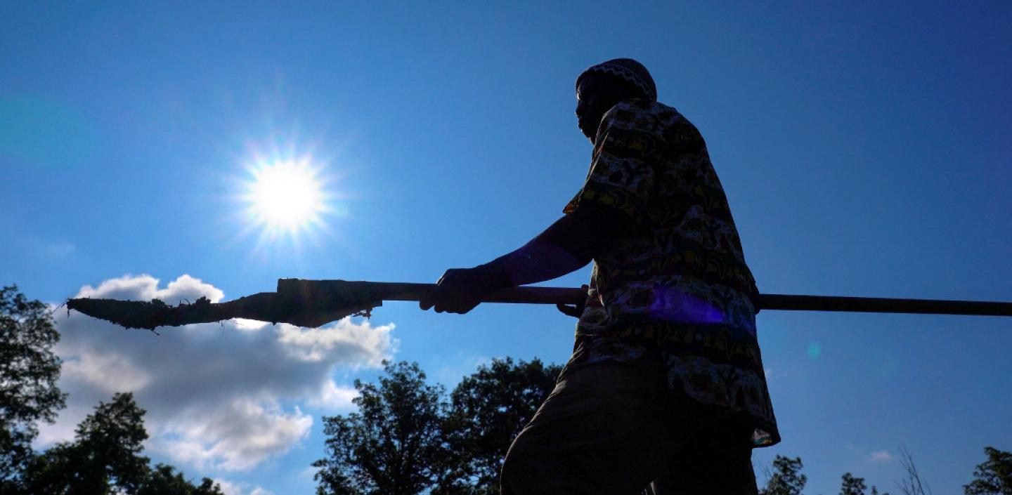 Silhouette of a man holding a farming tool