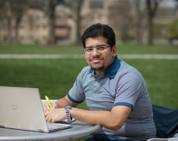 student ashraf bhuiyan sitting with computer outside.
