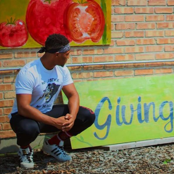 "Student stands in front of a ""Giving Garden"" mural"