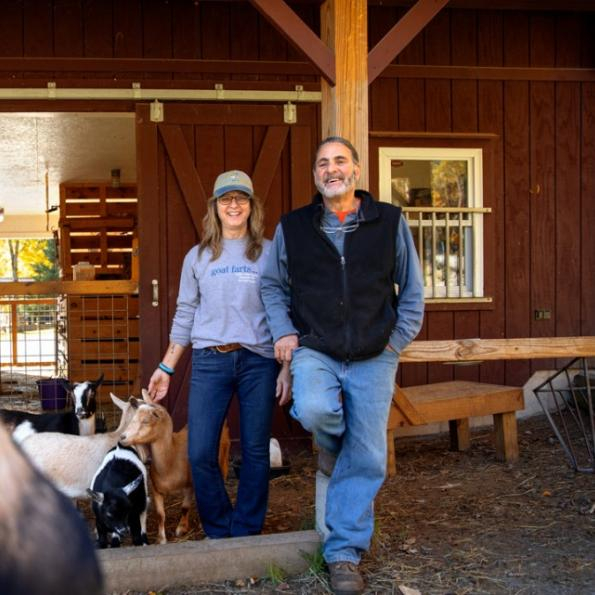 A man and woman standing with their back to a barn with small goats at their feed