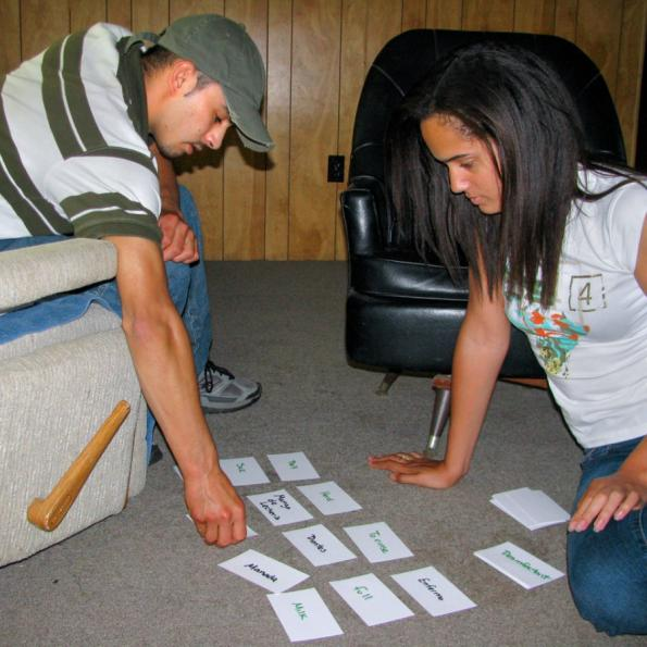 A female student sitting on the ground inside a room with a male sitting on a chair. Both are looking at flashcards laid out on the floor