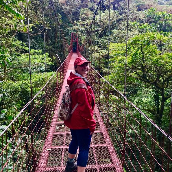A student on a bridge in a forest
