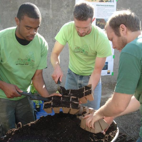 Three males put potting soil into seedling containers