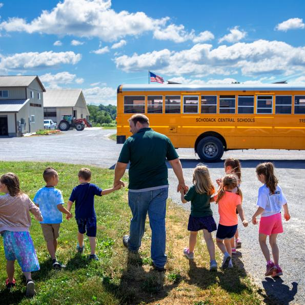 A male walks a group of children toward a school bus