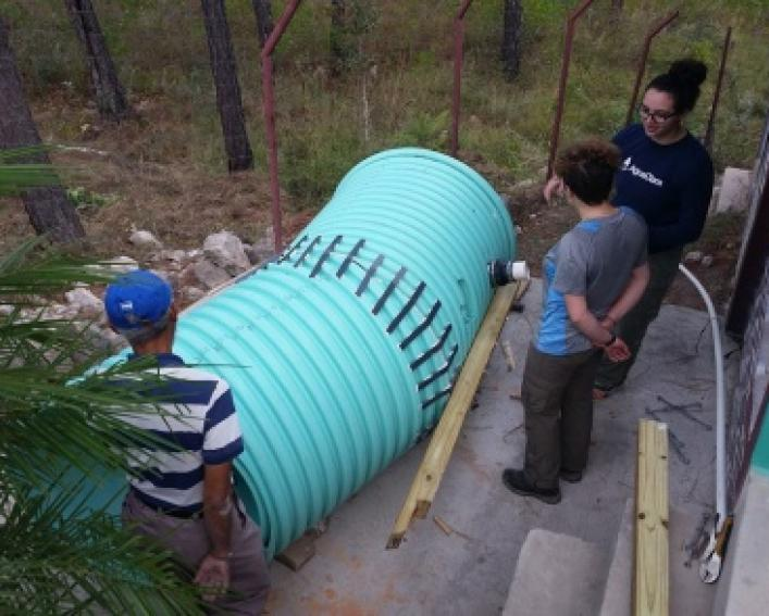 Zoe Maisel and Erica Marroquin install water purification system with Jorge Dueñas Carcamo
