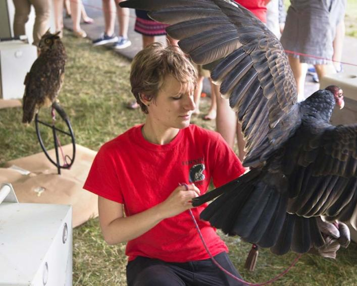 A female student holds a large raptor