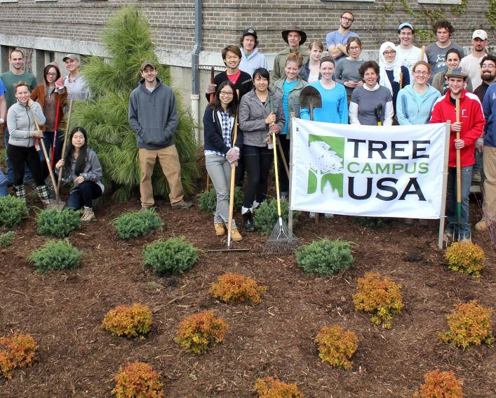 Group of students with newly planted landscape and Tree Campus USA sign