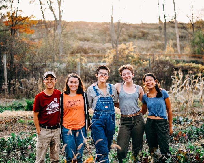 Student farm managers pose in field of vegetables