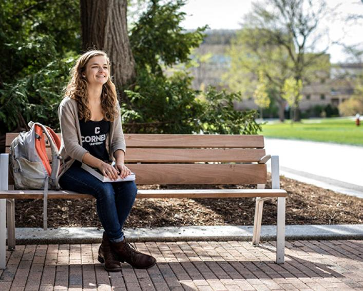 Plant sciences alum Hannah Fuller sits on bench outside Plant Science Building