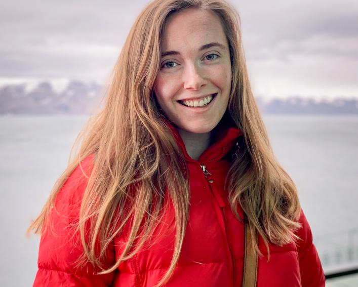 A woman in a red jacket smiles as she is photographed in front of water