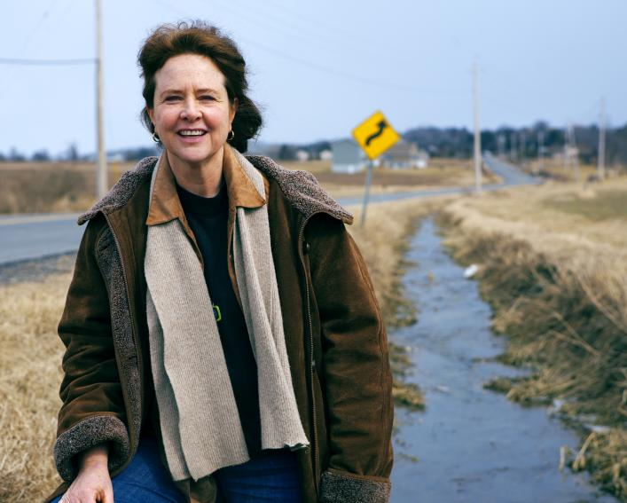 A woman stands next to a drainage ditch running along a rural highway