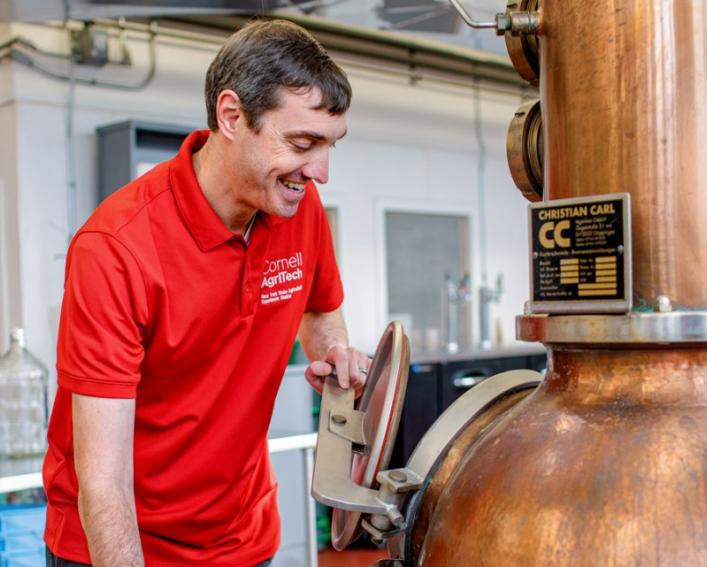 A man in a red shirt examines a copper distiller