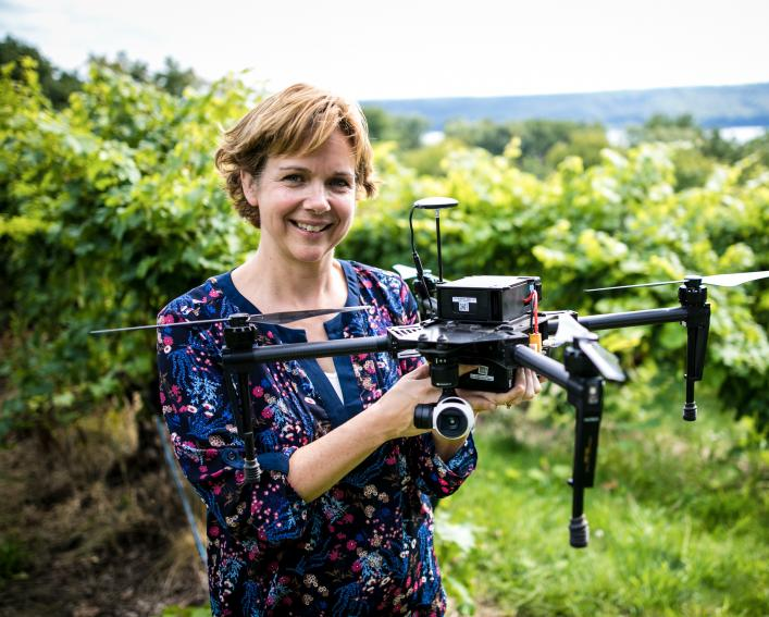 women holds drone while stnading in a vinyard