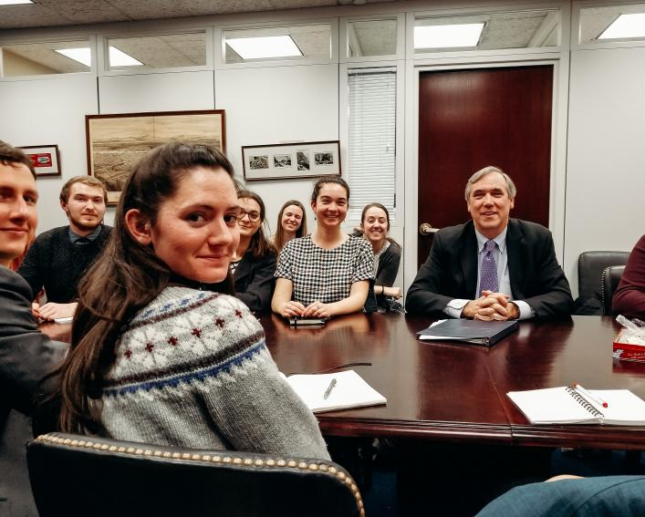A group of students in a conference room with Oregon Senator Jeff Merkley.