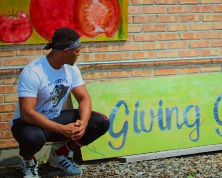 "a man kneels in front of a sign that reads ""giving garden"""