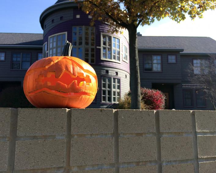 A pumpkin sits on a stone wall in front of the Akwe:kon program house.