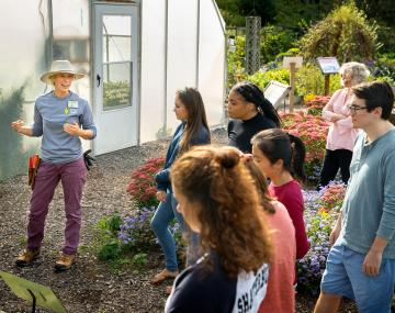 Youth learn about gardening at Cornell Botanic Gardens with greenhouse in background.