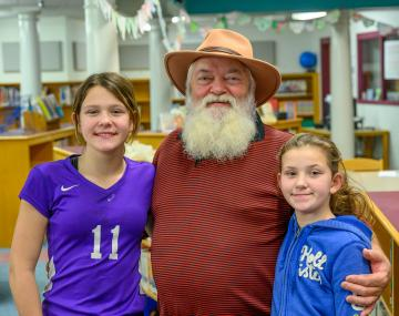a man with a long white beard stands with two children
