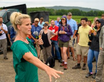 woman holding a microphone speaks to a crowd in a field