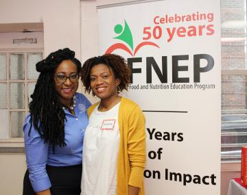 two people stand in front of a banner that reads FNEP