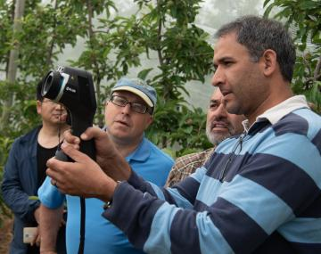 group of people watching a man in a striped shirt use technology