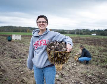A female student poses with a basket of harvested crops