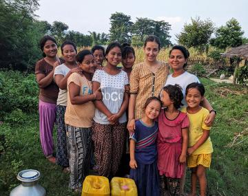 Women gather around containers of water in Nepal