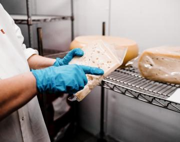 Extension aide holds vacuum-sealed artisan cheese.