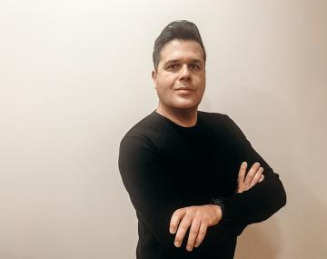 Elad Tako standing in a black sweater with his arms folded against a white wall