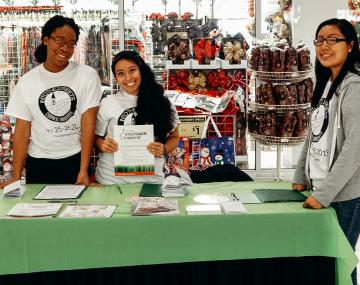 Three students display brochures and materials at a tabling event.